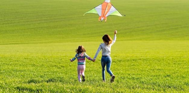 Teo kleine meisjes houden elkaars hand vast en rennen met vliegende kleurrijke vliegers op het groene veld