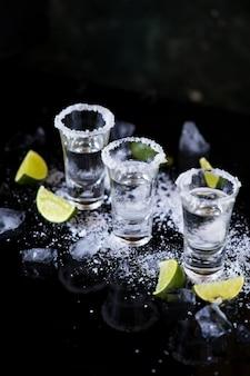 Tequila shot met limoen en zout op zwarte achtergrond