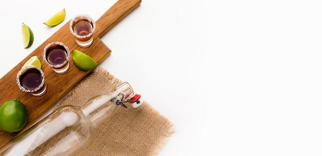 Tequila-shots van bovenaanzicht en limoenplakken met kopie-ruimte