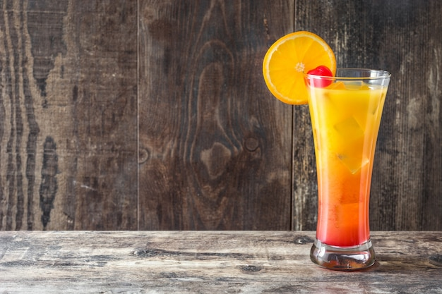 Tequila sunrise cocktail in glas op houten tafel met kopie ruimte