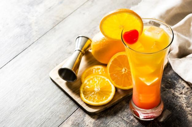 Tequila sunrise cocktail in glas op houten tafel
