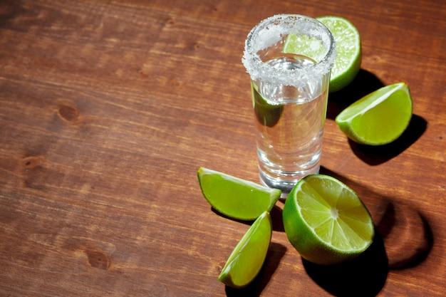 Tequila zilveren schoten met limoenplakken en zout op houten bord