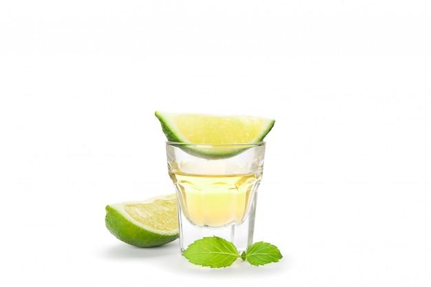 Tequilaschot met kalkplakken en munt op wit wordt geïsoleerd dat