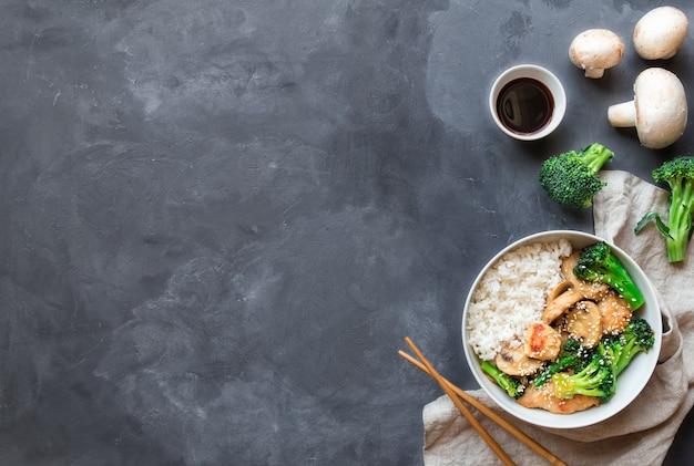 Teriyaki kip, broccoli en champignons roerbak met witte rijst in kom op grijze betonnen achtergrond. aziatische keuken. bovenaanzicht met ruimte voor tekst.