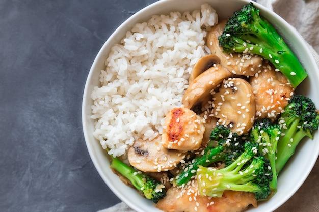 Teriyaki kip, broccoli en champignons roerbak met witte rijst in kom op grijze betonnen achtergrond. aziatische keuken. bovenaanzicht.