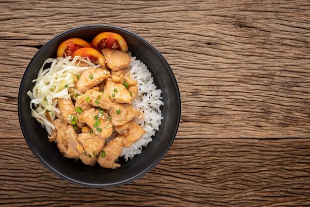 Teriyaki kip donburi, japans eten, gestreamde rijst met teriyaki kip, gehakt bloemkool, tomaat, lente-ui en sesam in zwarte keramische kom op rustieke houtstructuur achtergrond, bovenaanzicht