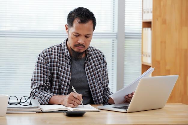 Terloops geklede aziatische man die in bureau werkt, in notitieboekje schrijft en documenten houdt