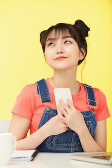 Terloops geklede aziatische vrouw die bij bureau zit, omhoog kijkt en smartphone omklemt naar de borst