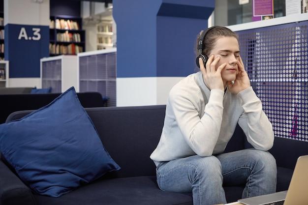Terloops geklede jongeman beoefenen van meditatie, luisteren naar muziek met een koptelefoon
