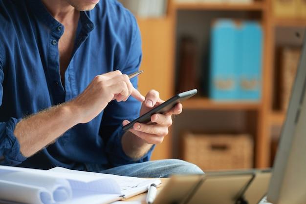 Terloops geklede onherkenbare man met behulp van smartphone op het werk op kantoor