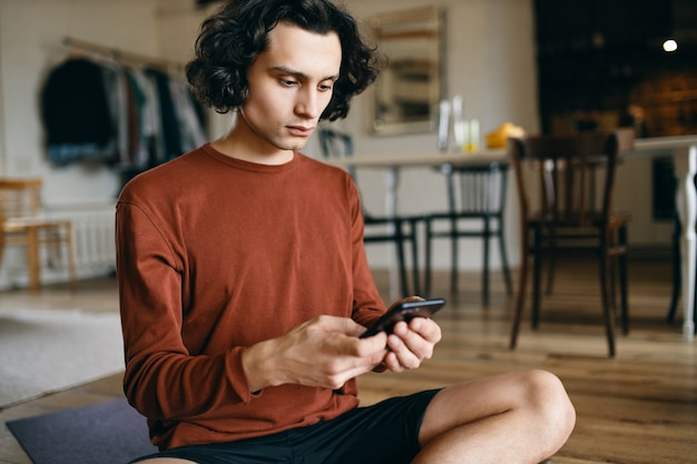 Terloops geklede serieuze jonge zakenman die mobiel sms'en sms of e-mail controleert terwijl hij op afstand werkt vanuit huis.