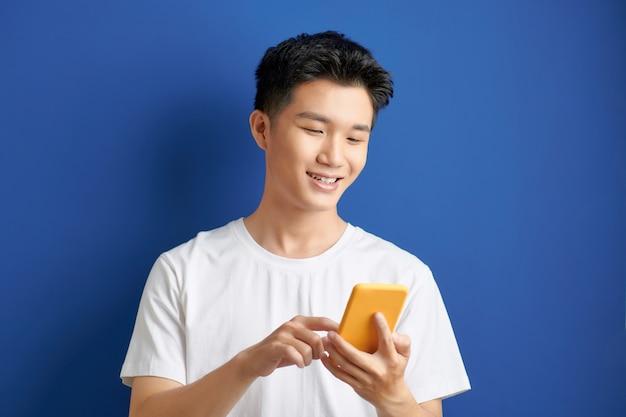Terloops geklede student status geïsoleerd op blauwe achtergrond kijken naar scherm van slimme telefoon