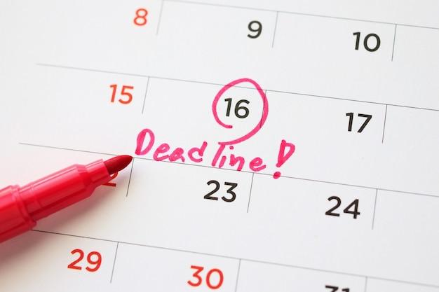 Termijn schrijven op witte kalenderpagina datum close-up
