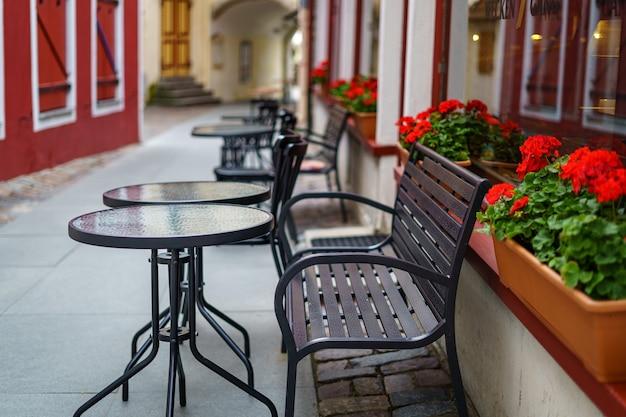 Terras met ronde glazen tafels en metalen stoelen om te relaxen en iets te drinken.