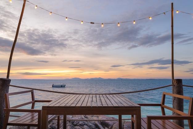 Terras met uitzicht op zee met houten tuinstoelen en een tafel
