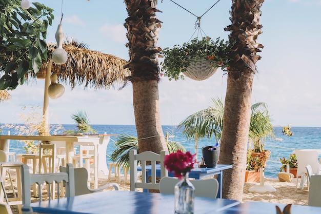 Terras met witte houten tafels en stoelen en palmbomen