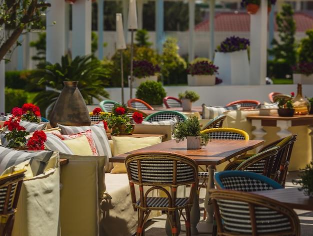 Terras open restaurant met banken, stoelen en tafels.