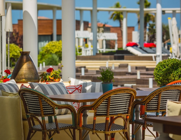 Terras van een hotel gevuld met zachte meubels in een groene ruimte.