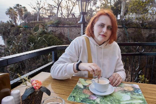 Terras van restaurant aan zee in antalya, turkije, jonge europese roodharige vrouw die aan tafel ontspant met een kopje koffie