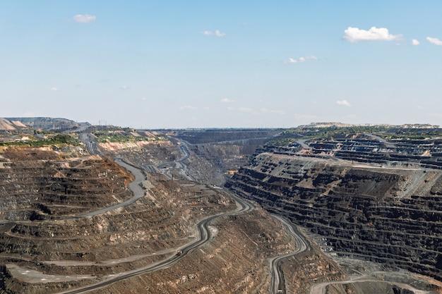 Terrasvormig reliëf van ijzerertsgroeve, mijnbouw, uitrusting voor mijnbouw en steengroeven, algemeen beeld