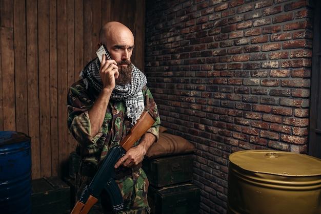 Terrorist in uniform houdt kalashnikovgeweer en mobiele telefoon in handen, mannelijke mojahed met wapen.