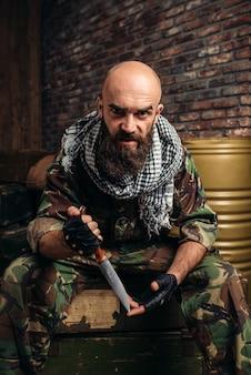 Terrorist in uniform met mes in handen zittend op dozen met munitie. terrorisme en terreur, soldaat in camouflage in wapenarsenaal