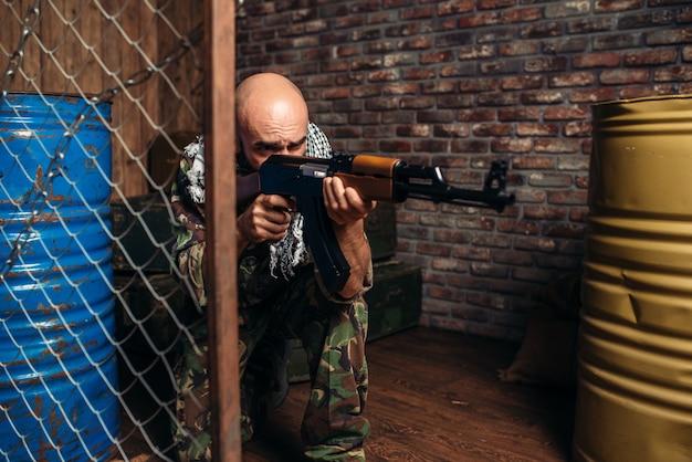 Terrorist in uniform schiet uit een kalashnikovgeweer, mannelijke mojahed met wapen.