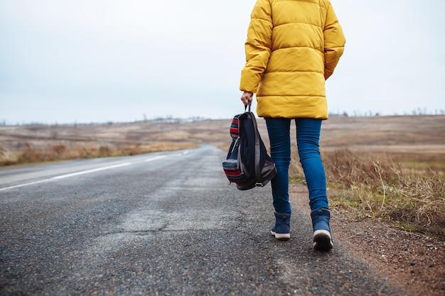 Terug close-up weergave van een vrouw die de eenzame weg loopt met een rugzak in haar hand.