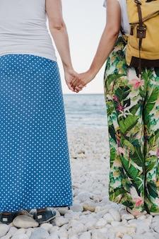 Terug en close-up weergave van lesbisch koppel hand in hand op het strand tijdens zonsondergang. liefde is liefde en lgtbi-concept