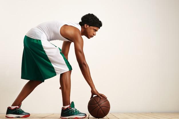 Terug geschoten foto van basketbalspeler die de bal aan zijn zijde op wit houdt