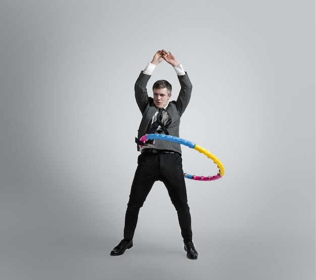 Terug in de kindertijd. tijd voor plezier. man in kantoorkleding training met kleurrijke hoepel op grijze muur. ongewone look voor zakenman in beweging, actie. sport, gezonde levensstijl, werken.