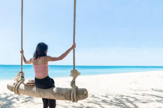 Terug mooie jonge aziatische vrouwen met een bruine huid draagt roze tank zwarte broek
