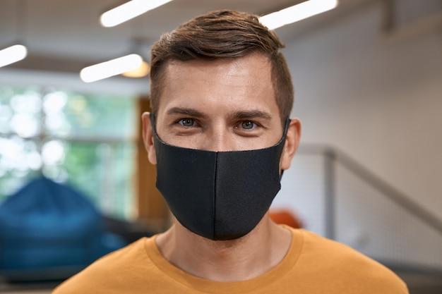 Terug naar kantoor close-up portret van jonge man mannelijke kantoormedewerker met zwart beschermend masker en