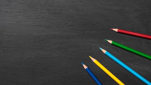 Terug naar school. accessoires kleurpotloden op schoolbord achtergrond. bovenaanzicht.