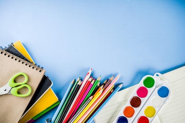 Terug naar school achtergrond met accessoires voor het schoollokaal - verven, potloden, schriften, boeken, schaar, krijt, stiften, blauwe achtergrond, boven exemplaarruimte