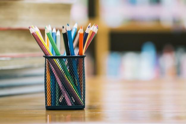 Terug naar school achtergrond met boek en houten kleurpotloden in de mand