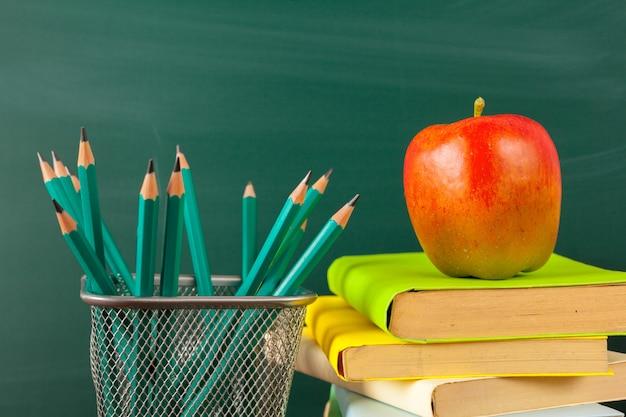 Terug naar school - appel en boeken met potloden en bord