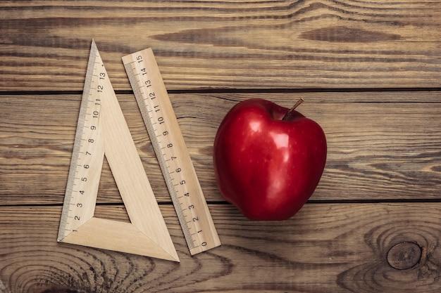Terug naar school. appel met linialen op een houten tafel