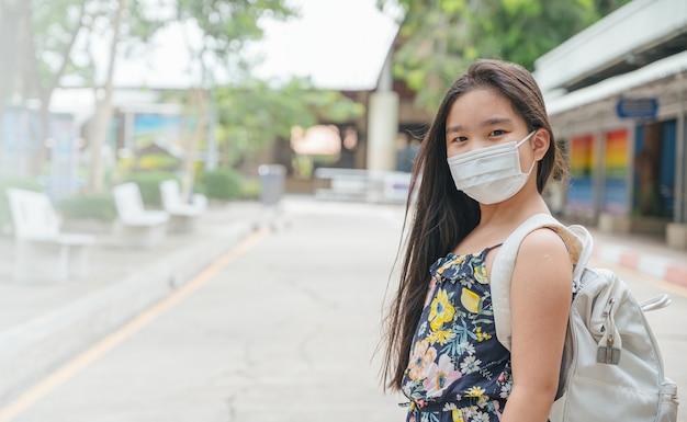 Terug naar school. aziatisch kindmeisje dat gezichtsmasker met rugzak draagt die naar school gaat. coronavirus pandemie. nieuwe normale levensstijl. onderwijs concept.