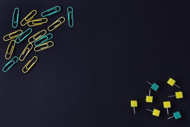 Terug naar school . clips en knoppen van gele en groene kleur op een zwarte achtergrond.