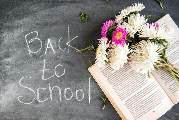 Terug naar school-concept. boek en astra bloemen op zwart bord. 1 september dag.