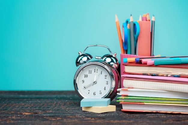 Terug naar school concept. boeken, kleurpotloden en klok