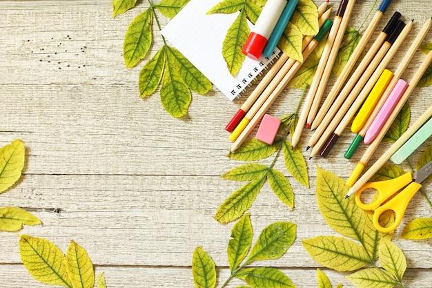 Terug naar school concept flatlay achtergrond tafel met herfstbladeren en verschillende schoolbenodigdheden