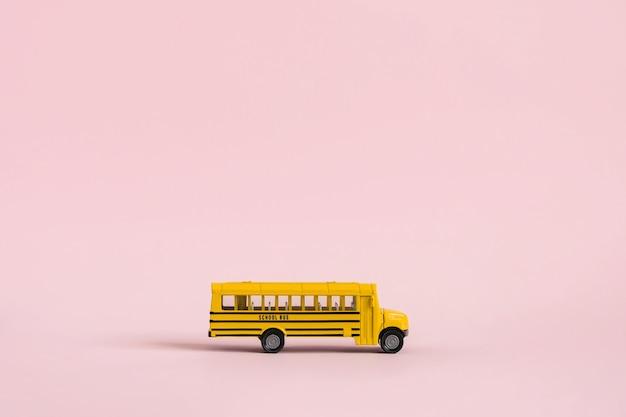 Terug naar school-concept. gele speelgoed model schoolbus op roze