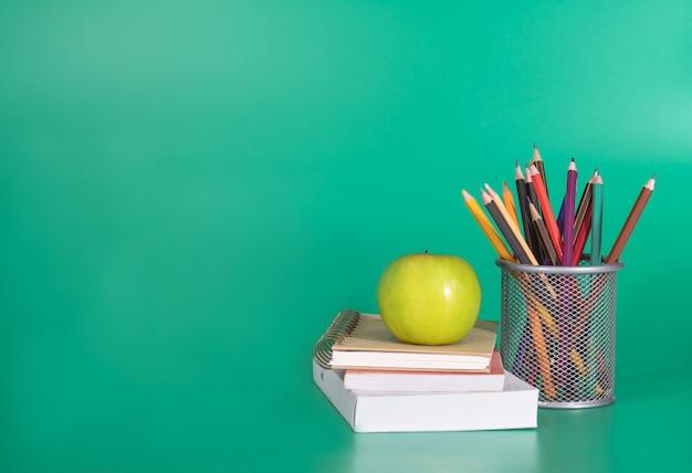Terug naar school concept. groene appel op het boek met schoolbenodigdheden