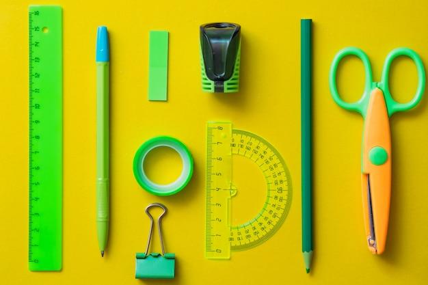 Terug naar school-concept. groene kantoorbehoeften op een gele achtergrond.