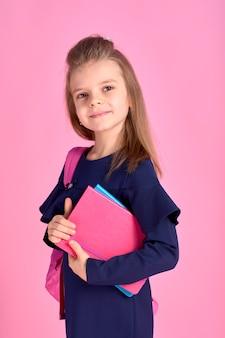 Terug naar school concept half gedraaide foto portret van mooie zelfverzekerde mooi slim meisje met schrift notebook dragen schooluniform jurk roze heldere rugzak geïsoleerd