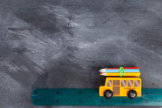 Terug naar school-concept. imitatie van reis naar school op schoolbus. potloden, liniaal, puntenslijper, speelgoedbus op zwarte achtergrond. bovenaanzicht. kopieer ruimte