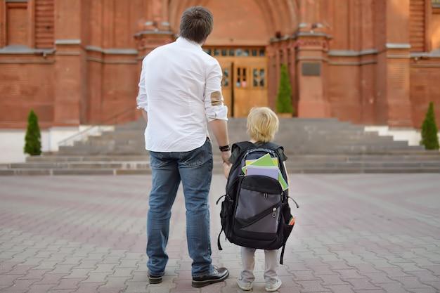 Terug naar school-concept. kleine leerling met zijn vader. eerste dag van de basisschool.
