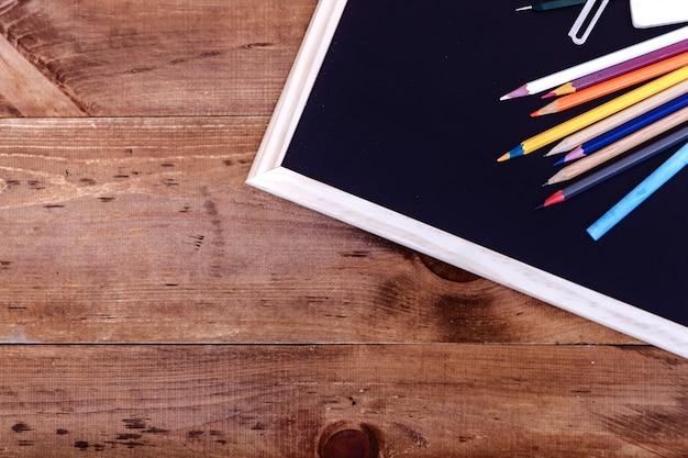Terug naar school concept, kleurpotloden op zwarte tafel, veelkleurige briefpapier accessoires voor opvoeder onderwijs kind puttend uit lege houten bureau, creatief onderwijs achtergrond, bovenaanzicht, kopie ruimte